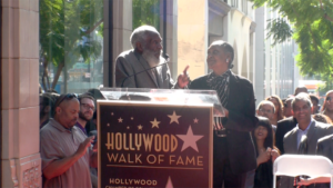 Dick Gregory addresses the onlookers with his wife Lillian at his side